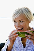 Woman eating watermelon by side of lake