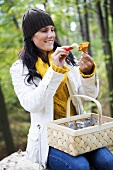 Woman cleaning chanterelle with brush in wood