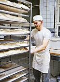Baker pushing a rack of bread