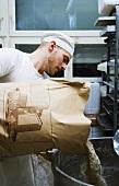 Baker tipping flour into vat