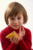 Little girl holding a puff pastry in her hand