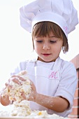 Little girl in chef's hat kneading dough
