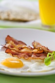 Fried bacon and egg with orange juice