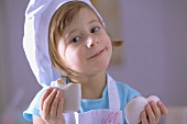Little girl in chef's hat eating heart-shaped gingerbread