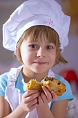 Little girl in chef's hat holding raisin biscuits