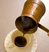 Pouring Turkish coffee into a cup