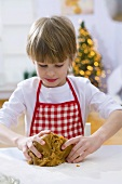 Little boy kneading dough for Christmas biscuits