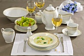 Place-setting with broccoli soup, salad and white wine