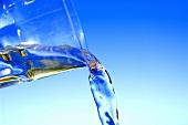 Wasser aus einem Trinkglas gießen