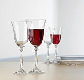 Glasses of red wine on table