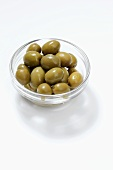 Green olives in small glass dish