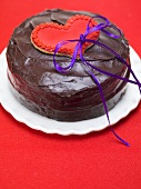 Chocolate cake with red heart-shaped biscuit and bow