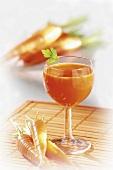 Carrot juice in glass, fresh carrots beside it