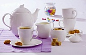 A cup of tea, amaretti, brown sugar and teapot