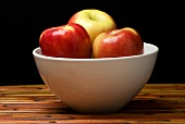 Fresh Apples in a White Bowl on Wood