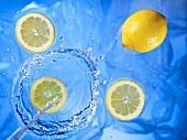 Wasserstrahl fließt auf Zitronen und Zitronenscheiben