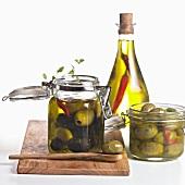 Eingelegte Oliven in Gläsern & eine Flasche Chiliöl