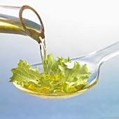 Oil running onto lettuce leaf on spoon