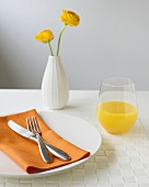 Place-setting with orange napkin, orange juice and flowers in vase