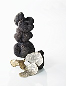 Black truffles, stacked, one partly sliced