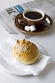 Milk roll with sugar, coffee, newspaper
