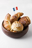 Croissants and sweet pastries with French flag in wooden bowl