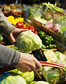 Person choosing vegetables at a market stall