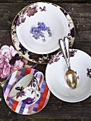 Plates, spoons and cups with saucers on a wood background
