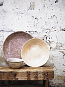 Old bowls on a wooden table on a wall