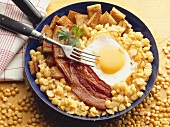 Fried egg and bacon on chick-peas
