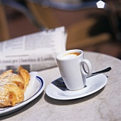 Caffè macchiato with brioche and newspaper