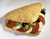 Sesame roll filled with tomato, mozzarella and basil