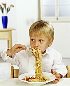 Boy eating spaghetti with tomato sauce