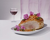 Roast pork with crackling, partly carved, with edible flowers