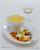Braised monkfish steak on vegetables with polenta