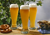 Three glasses of wheat beer on wooden table with pretzels & lard