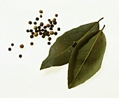 Two bay leaves, white and black peppercorns