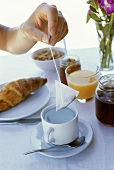Laid breakfast table: hand holding tea bag over teacup