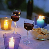 Glasses of red wine and crisps on candlelit table