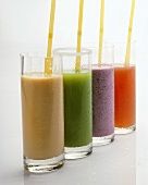 Four different fruit and vegetable juices in glasses