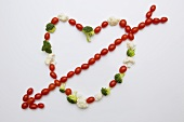 Tomatoes, broccoli and cauliflower forming heart with arrow