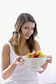 Girl holding a kitchen sieve with fresh fruit