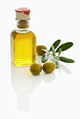 A small bottle of olive oil with olives and olive sprig