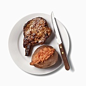 Pork Chop and Baked Sweet Potato on White Plate; White Background
