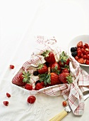 Fresh berries in a kitchen towel and in a bowl