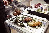 Placing the fried meat on a tray with herbs