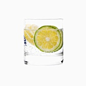 A glass of water with slices of lime