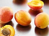 Mehrere Aprikosen, ganz und halbiert