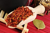 Safflower petals in a wooden scoop