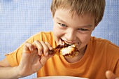 Young boy biting into a chicken drunstick